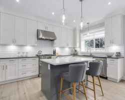 contemporary kitchen with white upper cabinetry and a grey island