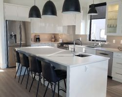 modern kitchen with white cabinetry, silver handles and black light fixtures